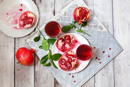 Pomegranate juice with fresh pomegranate fruits on wooden table. Healthy vitamin drink concept to raise hemoglobin top view Stockfoto - 129256789