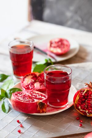 Pomegranate juice with fresh pomegranate fruits on wooden table. Healthy vitamin drink concept to raise hemoglobin close up Stockfoto - 129256794