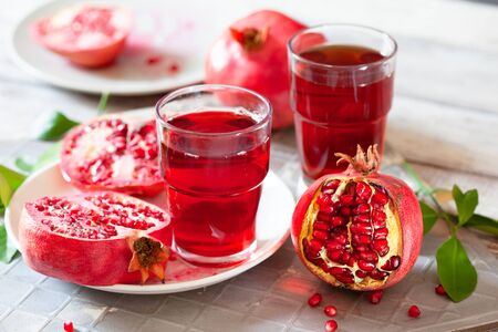 Pomegranate juice with fresh pomegranate fruits on wooden table. Healthy vitamin drink concept to raise hemoglobin close up Stockfoto - 129256793