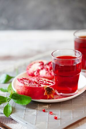 Pomegranate juice with fresh pomegranate fruits on wooden table. Healthy vitamin drink concept to raise hemoglobin close up Stockfoto - 129256795