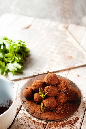Cocoa balls, chocolate truffle cakes on a black slate tray, sprinkled with cocoa powder. Process of cooking, copy space