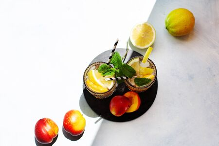 Peach summer cocktail with lemon and mint in direct sunlight top view 스톡 콘텐츠
