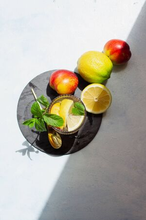Peach summer cocktail with lemon and mint in direct sunlight