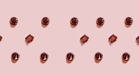 Chocolate praline with toffee filling pattern on pink backgound, chocolate backdrop