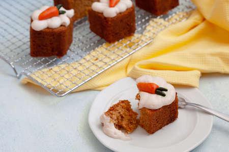 Vegan walnut carrot cake with cashew cream froasting, portions of pound cake on blue background