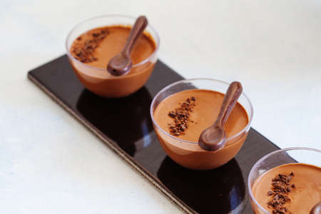 Chocolate low calorie mousse in portion glasses, fluffy vegan dessert with chocolate decorations Stockfoto