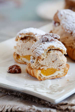 Classic French dessert Paris Brest, choux pastry filled with soft hazelnut cream, mango and passionfruit coulis