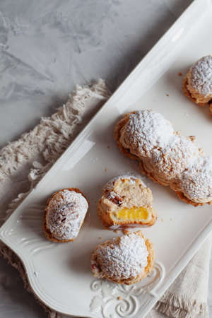Classic French dessert eclair, choux pastry filled with soft hazelnut cream mango and passionfruit coulis top view