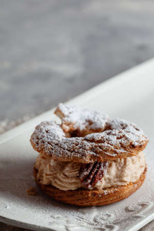 Classic French dessert Paris Brest, choux pastry filled with soft hazelnut cream, decorated with pecan and powdered with sugar powder