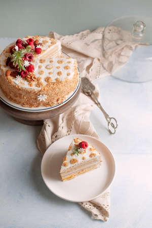 Tradional Russian cake Medovik, honey layered cake with hazelnuts decorated with fresh raspberry