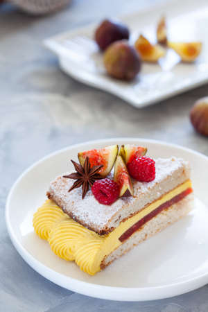 Modern savory dacquoise cake with figs and raspberry confit and mango cream, french cuisine, close up Stockfoto