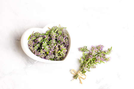 Thyme flowers in a white bowl on a light background close-up. The view from the top. Concept of folk medicine. Reklamní fotografie