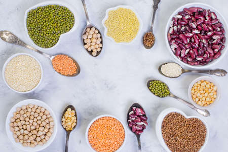 A variety of cereals and legumes on a light background. Lentils, red beans, quinoa, chickpeas, Munch, crushed peas, millet, buckwheat. Gluten-free products. The view from the top.