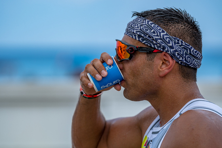 Young man drinking water during ironman