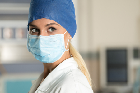 Young doctor in surgical mask in ICU