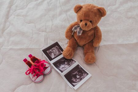 ?hildren shoes, fetal ultrasound and toy bear lay out on a light background.