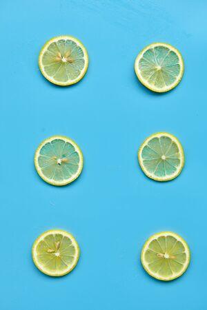 Composition with cut citrus fruits on blue background. Creative summer background composition with lemon slices. Minimal top down lemonade drink concept.Top view Banque d'images