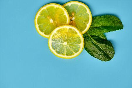 Composition with cut citrus fruits on blue background. Creative summer background composition with lemon slices, leaves mint and ice cubes. Minimal top down lemonade drink concept. Top view Banque d'images