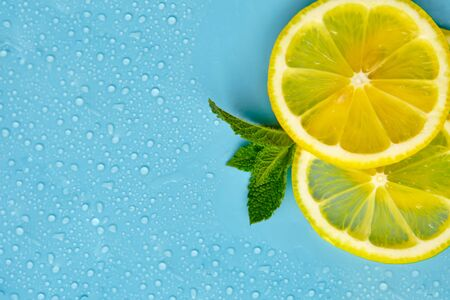 Composition with cut citrus fruits on blue background. Creative summer background composition with lemon slices, leaves mint and ice cubes. Minimal top down lemonade drink concept. Top view