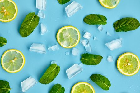 Composition with cut citrus fruits on blue background. Creative summer background composition with lemon slices, leaves mint and ice cubes. Minimal top down lemonade drink concept.Top view