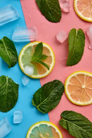 Composition with cut citrus fruits on color background. Creative summer background composition with lemon slices, leaves mint and ice cubes. Minimal top down lemonade drink concept.Top view