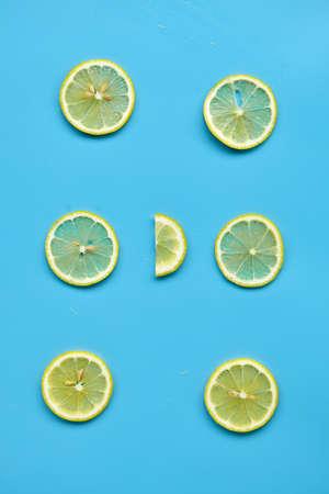 Composition with cut citrus fruits on blue background. Creative summer background composition with lemon slices. Minimal top down lemonade drink concept.Top view