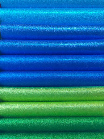 Colorful rolls of paper are spread out on the shelf. Accessories for flower shops. Multi-colored wrapping paper.