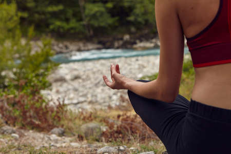 Yoga classes in nature. The concept of playing sports alone. Social exclusion. A woman does yoga on rocks, near a mountain river flows