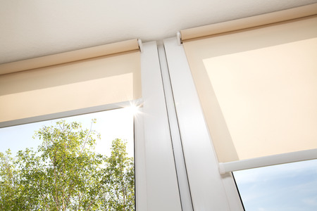 a blind: Window with sand coloured roll blinds
