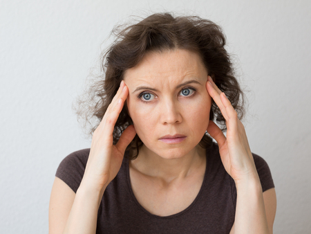 distressing: Woman thinking about seriously or with headache
