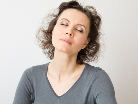 Woman 30-40 years old with closed eyes in meditation