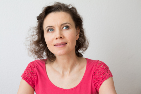 Happy woman with attractive smile thinking about Фото со стока