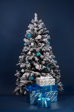 Christmas tree decoration on dark blue with gift boxes