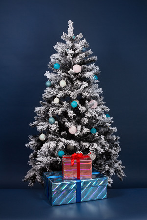 New year tree decoration on dark blue with gift boxes