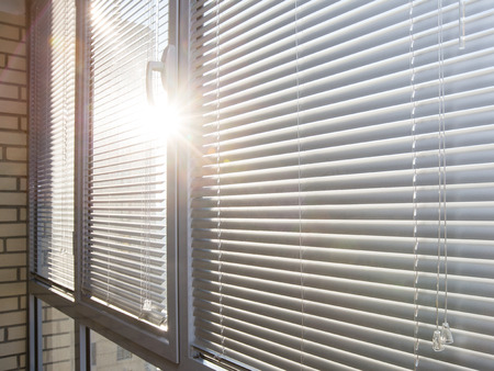 Closed aluminum window on sunny day with horizontal plastic blinds