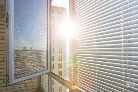 Otworzył okno na słoneczny dzień z poziomych żaluzji z tworzyw sztucznych Zdjęcie Seryjne