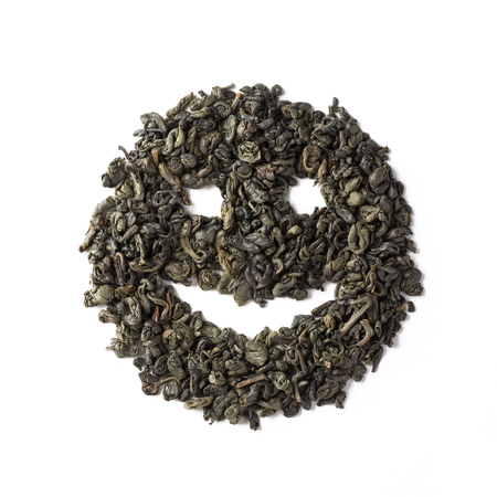 Green tea dried leaves placed in a form of smile Banque d'images