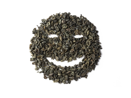 Green tea dried leaves placed in a form of smile Фото со стока
