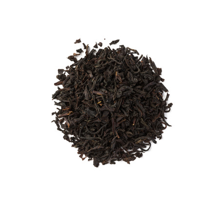 Black tea dried leaves placed in round form of circle, top view, isolated on white