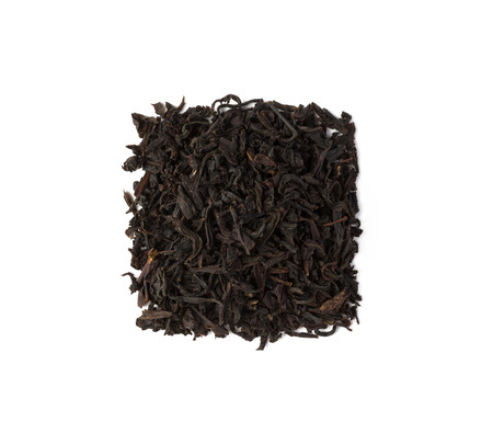 Black tea dry leaves placed in a form of square isolated on white