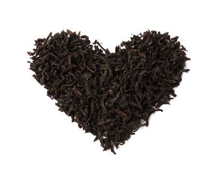 Black tea dry leaves placed in a form of heart isolated on white