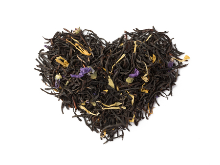 Black herbal flower tea dry leaves placed in a form of heart isolated on white