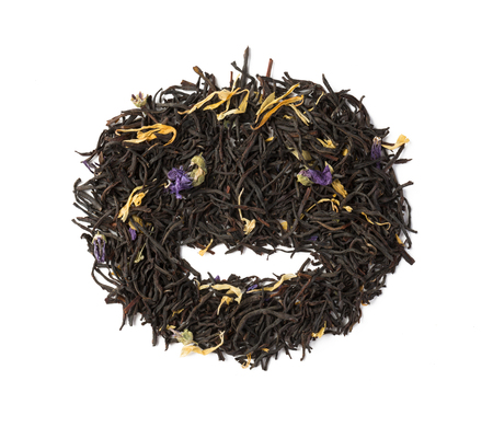 Black herbal flower tea dry leaves placed in a form of smile isolated on white Banque d'images