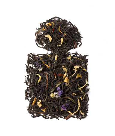Black herbal flower tea dry leaves placed in a form of perfume bottle isolated on white