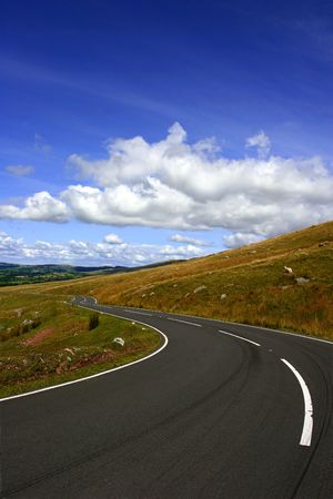 A rural mountain road with a left hand bend showing skid marks with a blue sky and clouds. photo