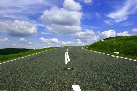 View of a mountain road from a low angle with a right hand bend in the distance against a blue sky with clouds. Stock Photo
