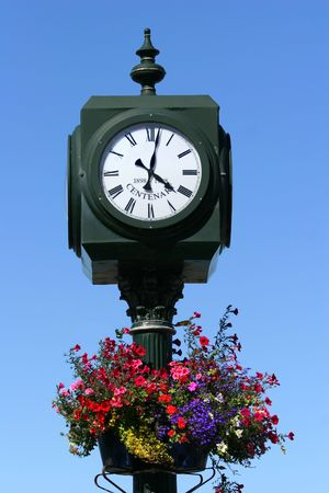 centenary: An old centenary metal street clock with a white face and roman numerals, with colorful flowers in a metal pot, set against a clear blue sky.