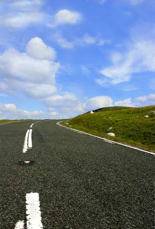 defining: Mountain road in the Brecon Beacons National Park, Wales, United Kingdom, from a low angle with a right hand bend in the distance, set  against a blue sky with puffy white clouds.