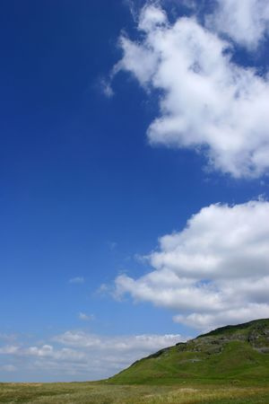 hillside: A hillside adjoining a plain with a blue sky full of puffy white clouds. Set in the Brecon Beacons National Park, Wales, United Kingdom. Stock Photo