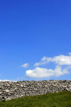 Old stone wall in a field with a blue sky and white clouds. photo